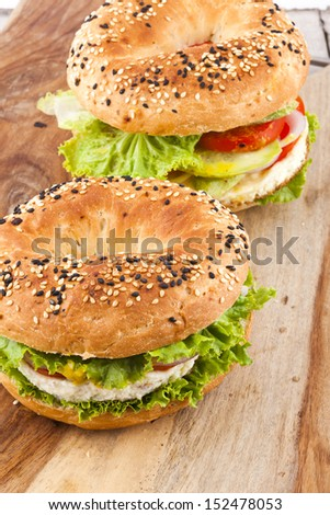 Fresh bagel sandwich over woden background - stock photo