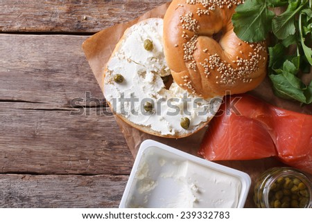 Fresh bagel with cheese, red fish and ingredients on the table. top view horizontal close-up  - stock photo