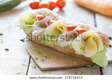 Fresh baguette with ham and cheese  - stock photo