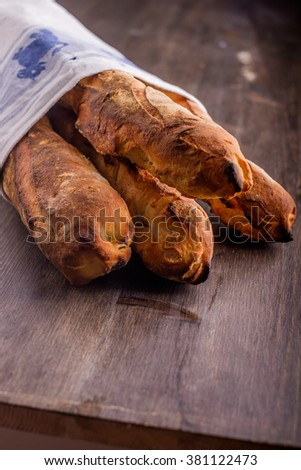 Fresh baked baguettes lined in a kitchen towel - stock photo