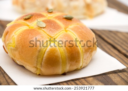 Fresh baked bread or bun with sunflower seeds topping on wood background - stock photo