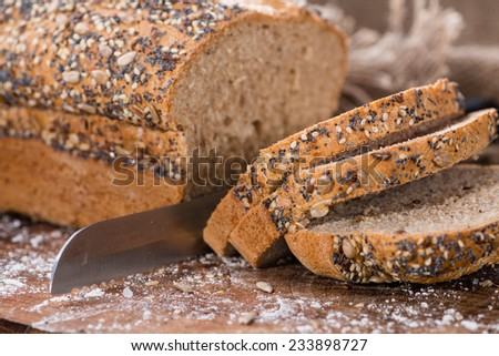 Fresh baked bread with seeds on rustic wooden background - stock photo