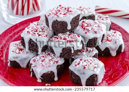 Fresh baked chocolate brownie bites covered with white icing and candy cane sprinkles stacked on festive red plate - stock photo