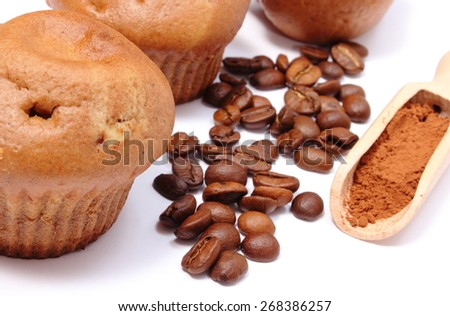 Fresh baked coffee muffins, coffee grains and powdery cinnamon on wooden spoon. Isolated on white background - stock photo