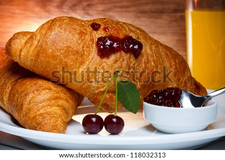Fresh baked croissants with cherry jam and juice - stock photo