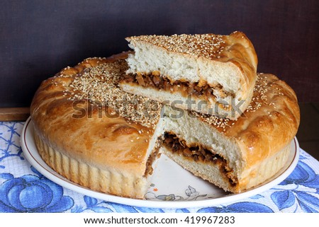 Fresh baked flavored homemade round cabbage pie with cutting section on the top, sliced, portion on the dark brown wooden background, just from oven, selective focus, close up - stock photo