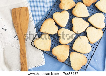 Fresh baked heart shaped cookies on cooling rack. - stock photo