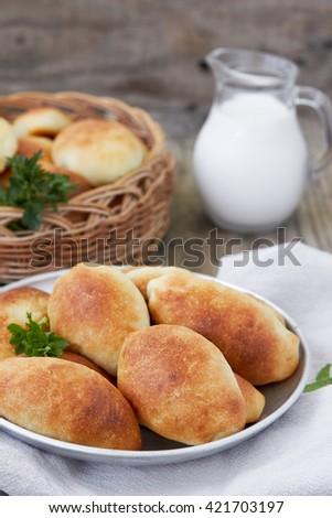 Fresh baked pasties and jug of milk. - stock photo
