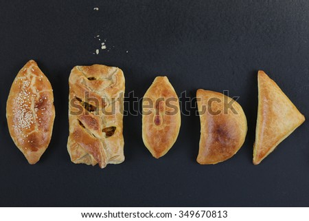 Fresh baked pasties filled with chicken,meat,mushrooms,spinach and cabbage - stock photo