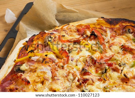 Fresh baked pizza with ham, peppers and cheese on a baking sheet, close-up as detail for Italian food - stock photo