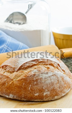 Fresh baked round artisan bread with rolling pin and flour jar in the background - stock photo