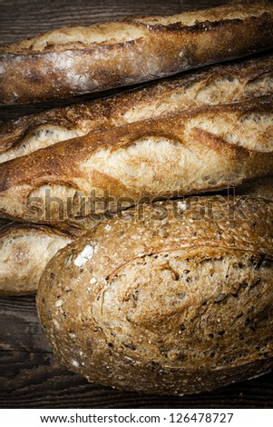 Fresh baked rustic bread loaves on dark wood background - stock photo