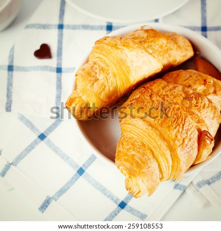Fresh baked tasty croissant with chocolate heart close up on white checked background. Instagram color effect. - stock photo