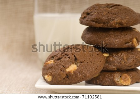 Fresh baked triple chocolate chip cookies with a glass of milk - stock photo