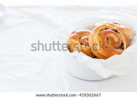 Fresh baked vanilla sweet sugar buns with chocolate drops in a bowl on a table with textile, with free space for text - stock photo