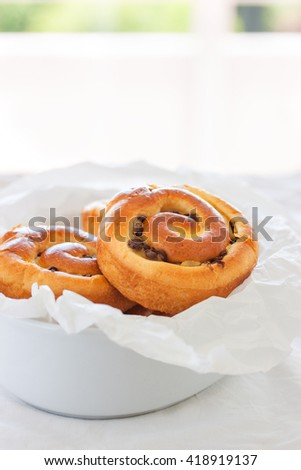 Fresh baked vanilla sweet sugar buns with chocolate drops in a bowl on a wooden background, closeup - stock photo