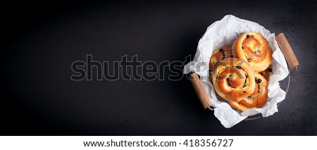Fresh baked vanilla sweet sugar buns with chocolate drops in a crate on a black wooden background, top view, with free space for text, horizontal - stock photo