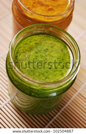 Fresh basil pesto and tomatoes sauce, typical italian dressing for pasta - stock photo