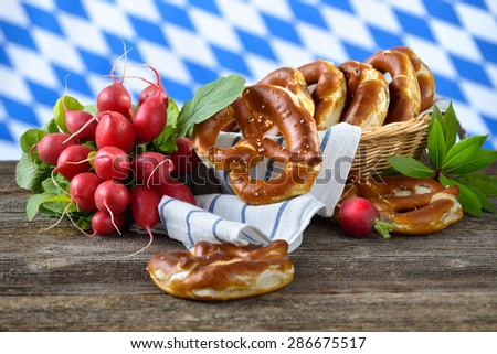 Fresh Bavarian pretzels in a breadbasket and a bunch of red radishes on a wooden table, in the background the white-blue flag of Bavaria - stock photo