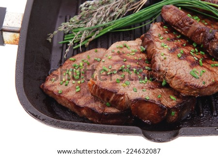 fresh bbq red meat with thyme and cayenne pepper on barbecue pan isolated on white background - stock photo