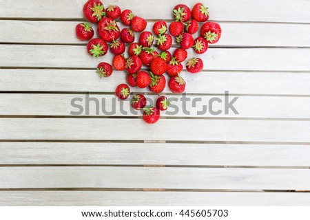 Fresh beautiful strawberries in the shape of a heart on a white wooden table. Background for Valentine's Day. Natural strawberry from the fruit garden. - stock photo