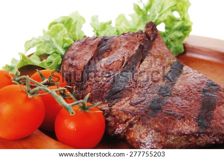 fresh beef steak grilled barbecue fillet on wooden dish with vegetable green salad and cherry tomatoes isolated over white background - stock photo