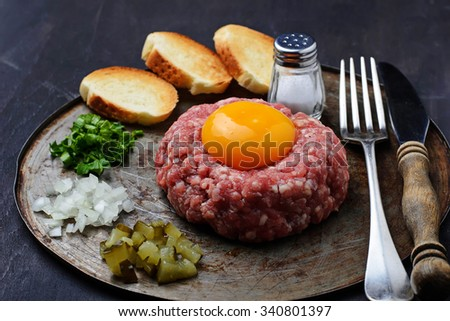 Fresh beef tartar with egg, pickled cucumber and onion. Selective focus - stock photo