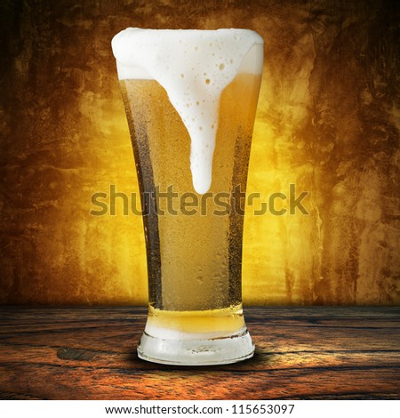 Fresh beer in glass with foam spills on yellow background - stock photo