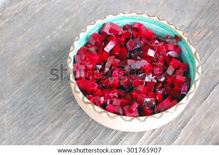 fresh beetroot salad in ceramic bowl on rustic wooden table - stock photo