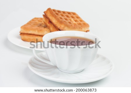 Fresh belgian waffles served on tabledesk with cup of tea - stock photo