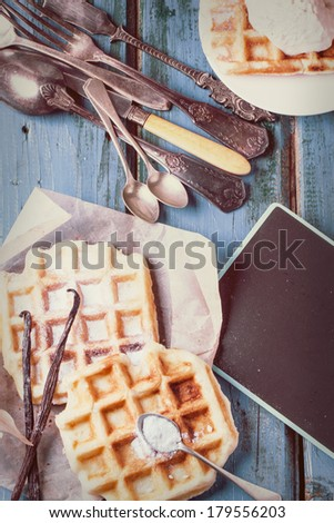Fresh belgian waffles served with vanilla sticks and vintage cutlery over blue wooden table in instagram filter effect. See series - stock photo