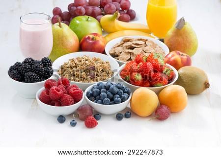 fresh berries, fruit and muesli for breakfast on white wooden table, horizontal - stock photo