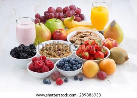 fresh berries, fruit and muesli on white wooden table, horizontal - stock photo