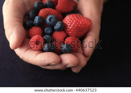 Fresh berries in a man's hands on a black background - stock photo