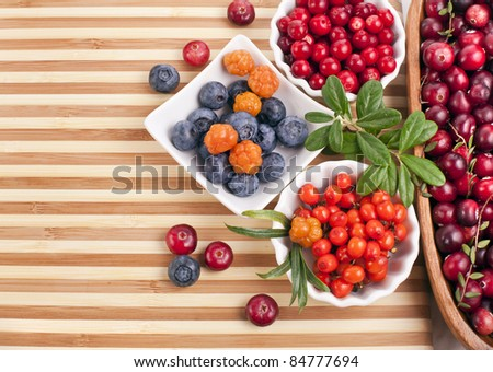 Fresh berries in a  wooden striped surface - stock photo