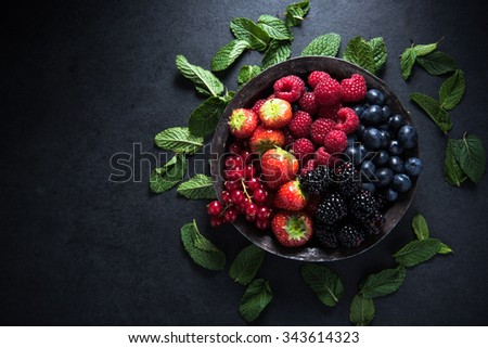 Fresh berries in rustic bowl, antioxidant concept, food border background - stock photo