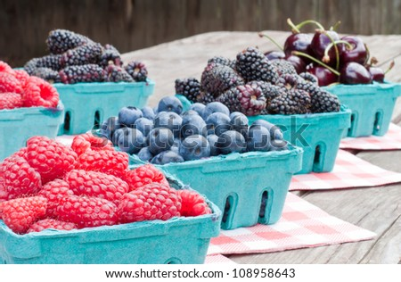 Fresh berries inn individual baskets placed on a table at the local market, focus on red raspberries - stock photo