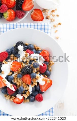 fresh berries, yogurt and homemade granola for breakfast, vertical, top view - stock photo