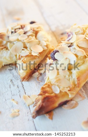 Fresh berry and almond pinwheel pastry, sprinkled with icing sugar on a brown wooden serving board with copy space - Shallow Depth of Field (DOF) - stock photo