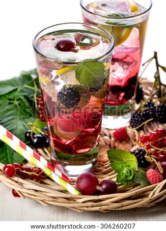 Fresh berry lemonade with red currant, gooseberry and blackberry - stock photo