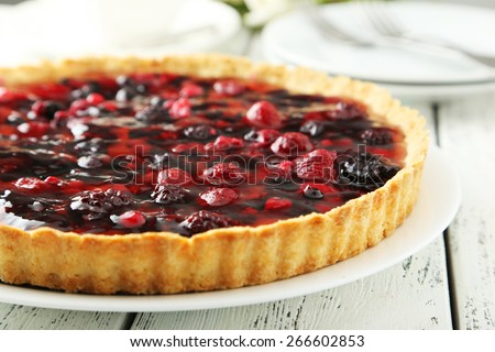 Fresh berry tart on plate on white wooden background - stock photo