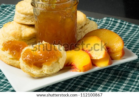 Fresh biscuits or scones with peach slices and jelly - stock photo