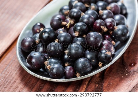 Fresh black currant on a wooden table - stock photo