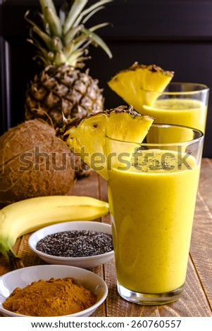 Fresh blended fruit smoothies made with pineapple, banana, coconut, turmeric and chia seeds surrounded by raw ingredients in drinking glass and pineapple slice garnish - stock photo