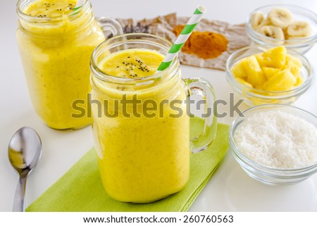 Fresh blended fruit smoothies made with pineapple, banana, coconut, turmeric and chia seeds surrounded by raw ingredients green straws - stock photo