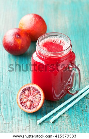 Fresh blood oranges juice in glass jar, selective focus - stock photo