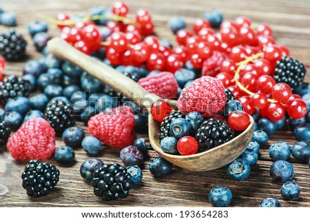 fresh blueberries, currants, blackberries, cranberries and raspberries. Focus berries in spoon - stock photo
