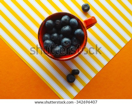 Fresh blueberries in a small cup on yellow stripes on orange background - stock photo
