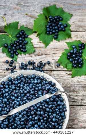 Fresh blueberries in basket on wooden table, ripe fruits from forest on farmer market, copy space, top view - stock photo