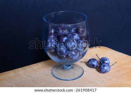 Fresh blueberries in beautiful small glass on the wooden table. Raw berries on black background - stock photo